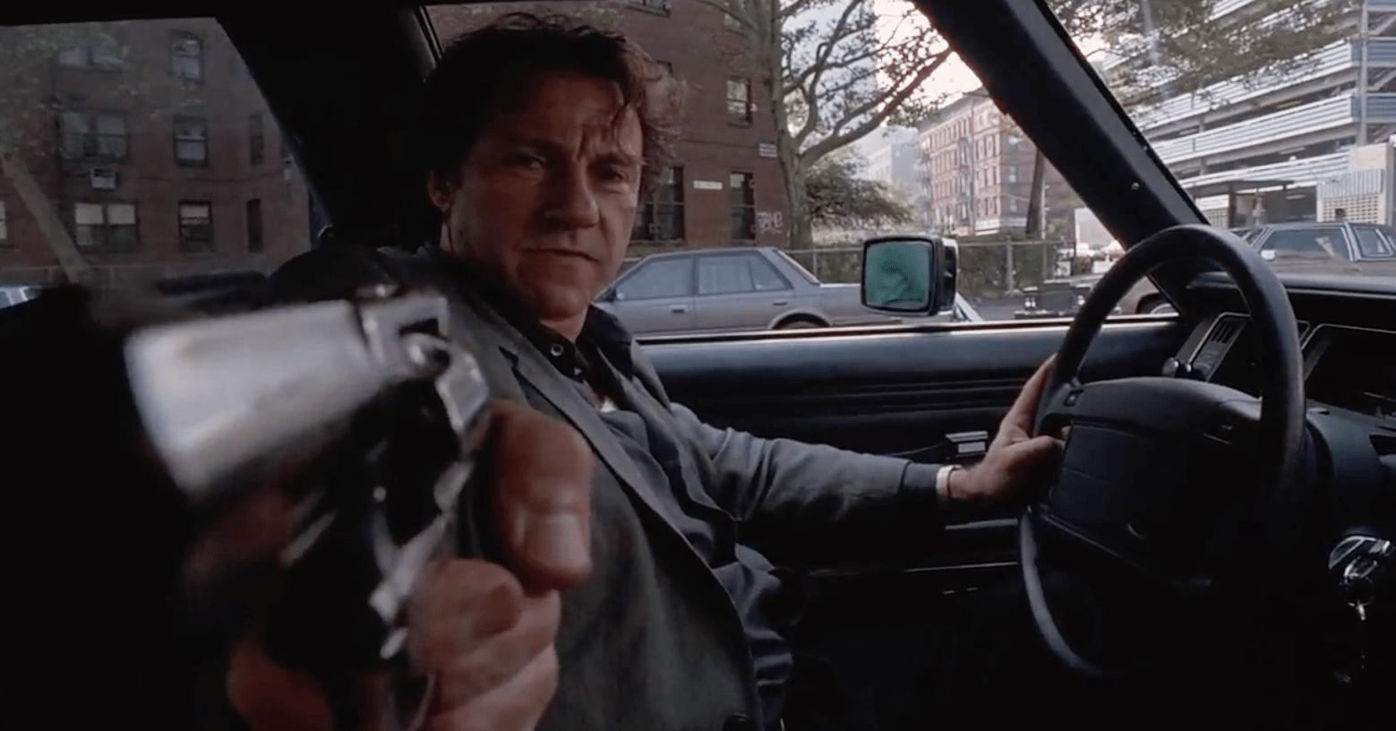 """Frame dal film """"Il cattivo tenente"""" di Abel Ferrara, Harvey Keitel in macchina punta la pistola vetro lo spettatore"""